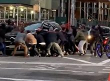 Passersby lift SUV off woman trapped under SUV on the streets of New York City