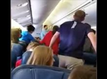 High school choir stand up to sing hymn as fallen U.S. soldier is carried off plane
