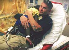 Photo of police officer snuggling abandoned toddler in hospital bed goes viral