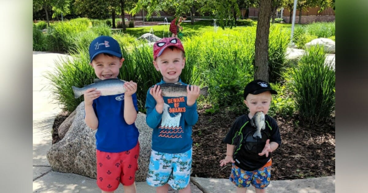 Toddler shoves rubber fish in mouth while his brothers pose for sweet family photo